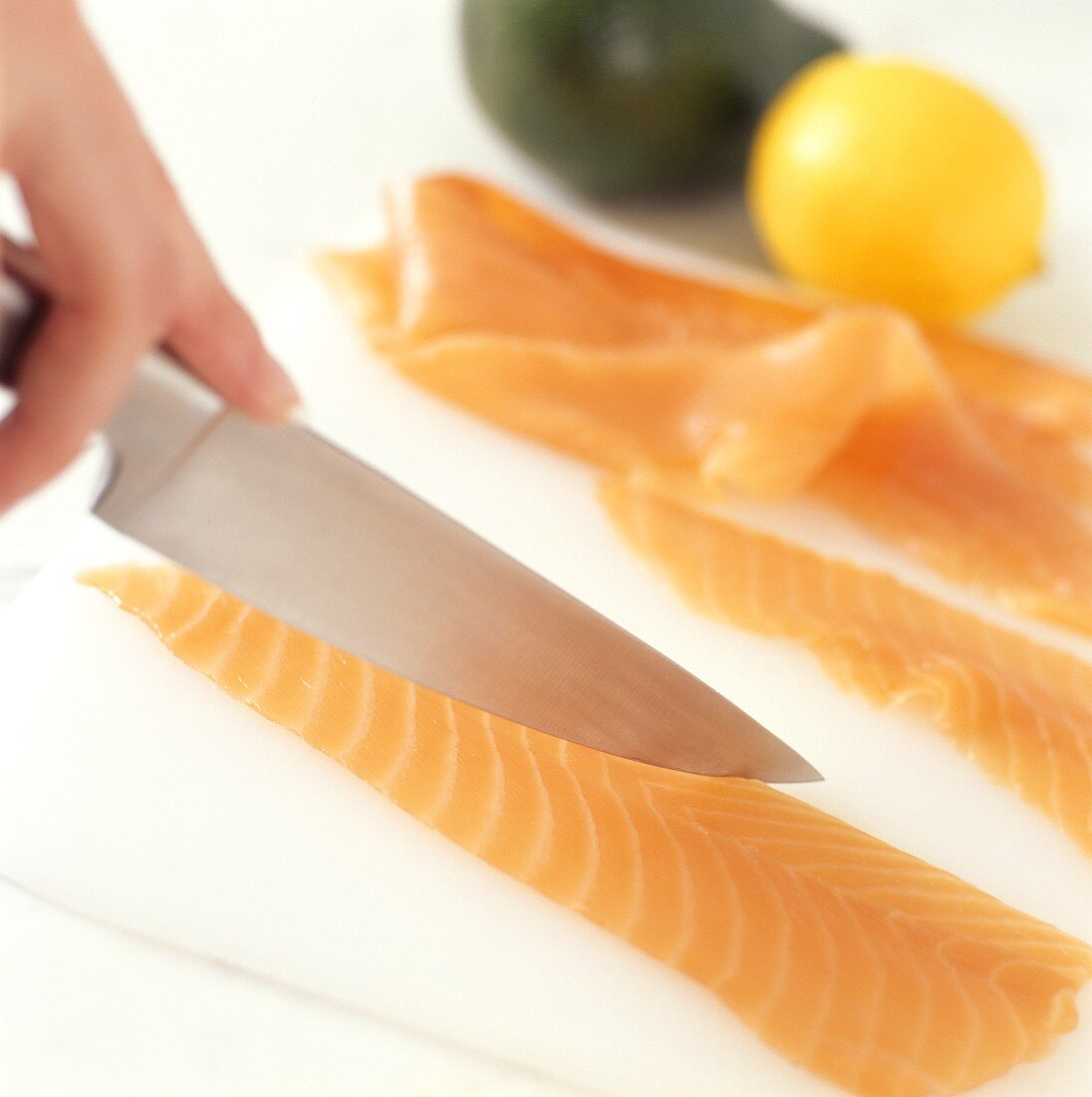 Salmon fillet being cut with a knife (for sushi)