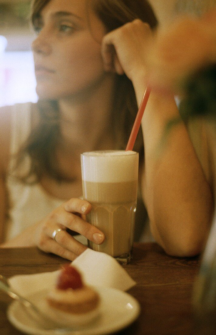 Woman with a glass of milky coffee in café