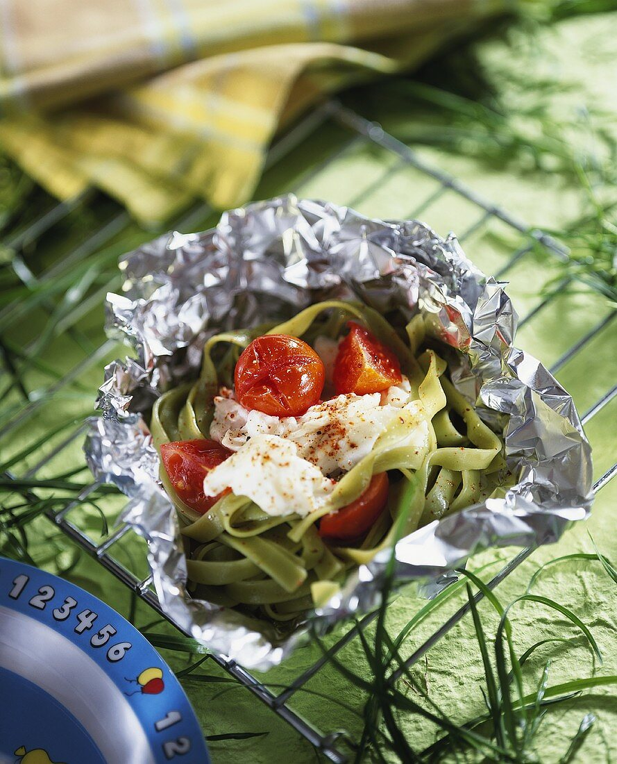 Green ribbon pasta with cod and tomatoes in aluminium foil