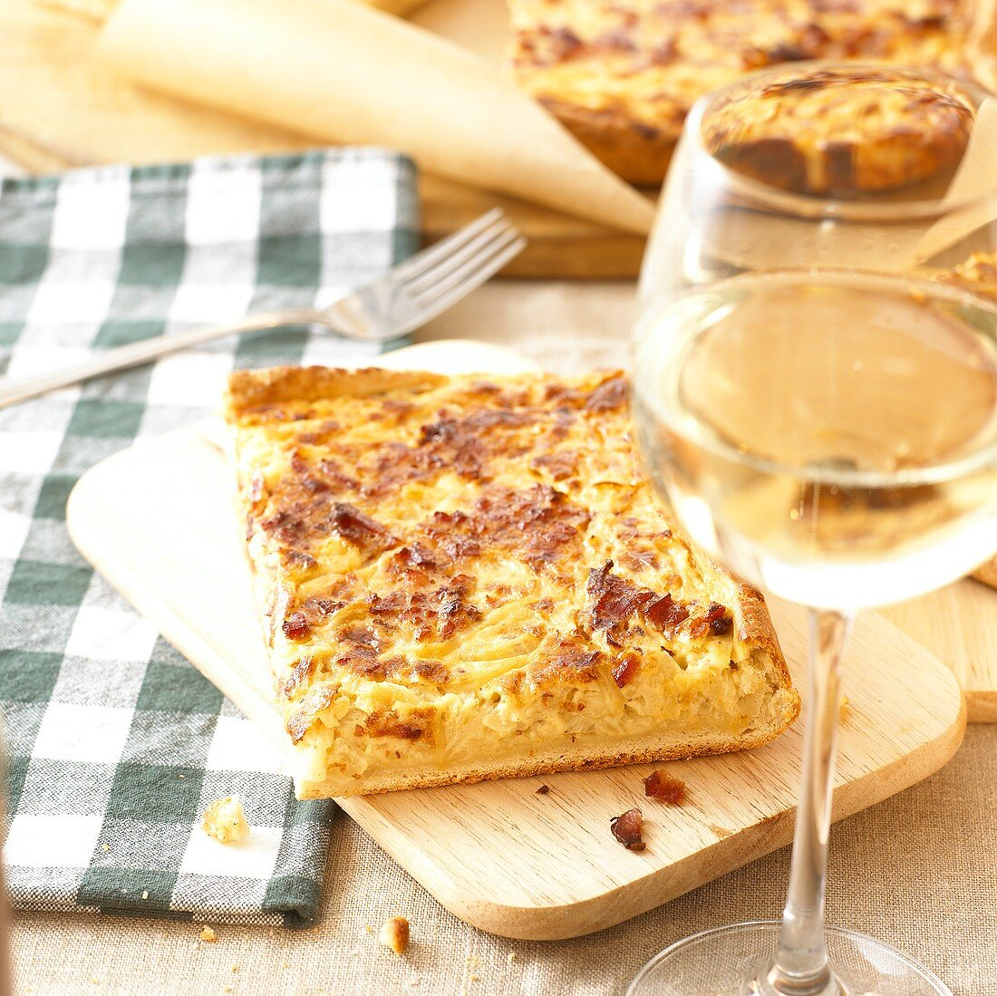 Onion quiche with bacon on chopping board; glass of white wine