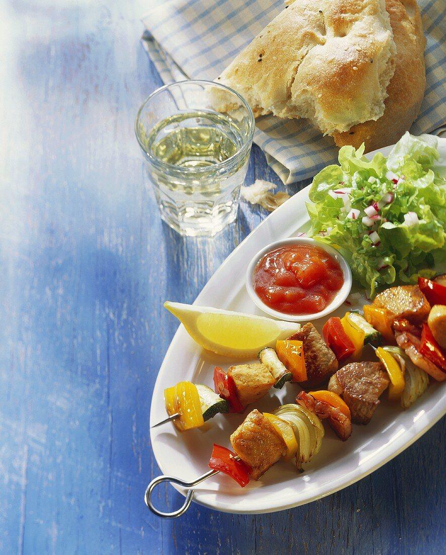 Skewered meat & vegetables with dip and salad leaves