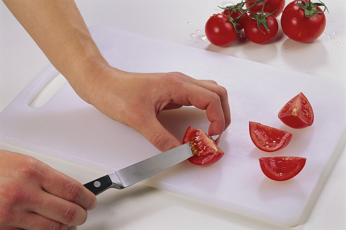 Cutting the flesh out of quartered tomatoes