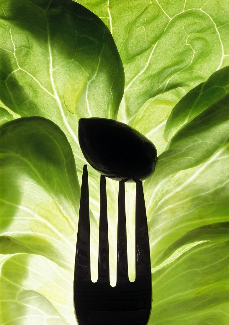 Lettuce leaf with an olive (close-up)