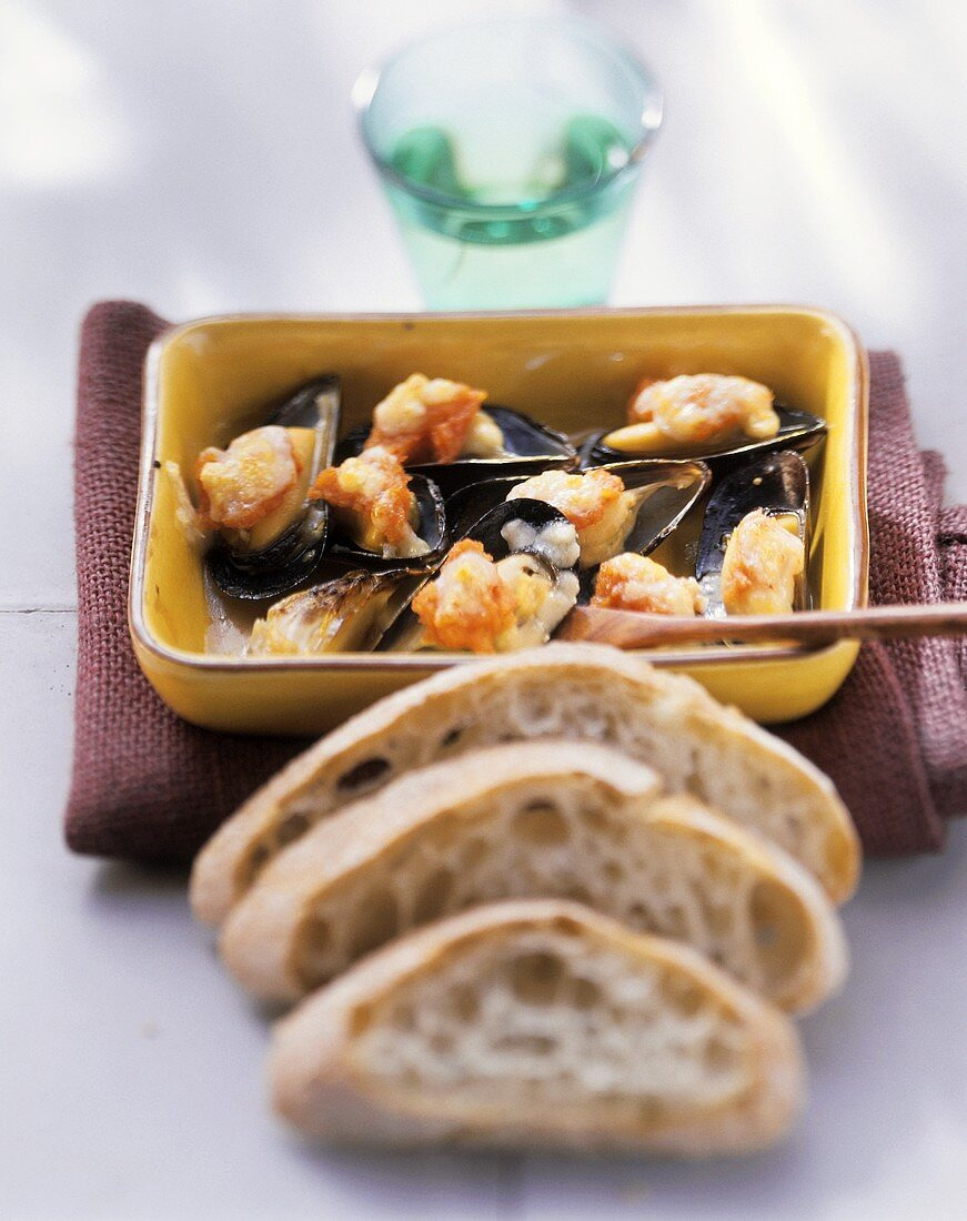 Mussel gratin, slices of bread in front
