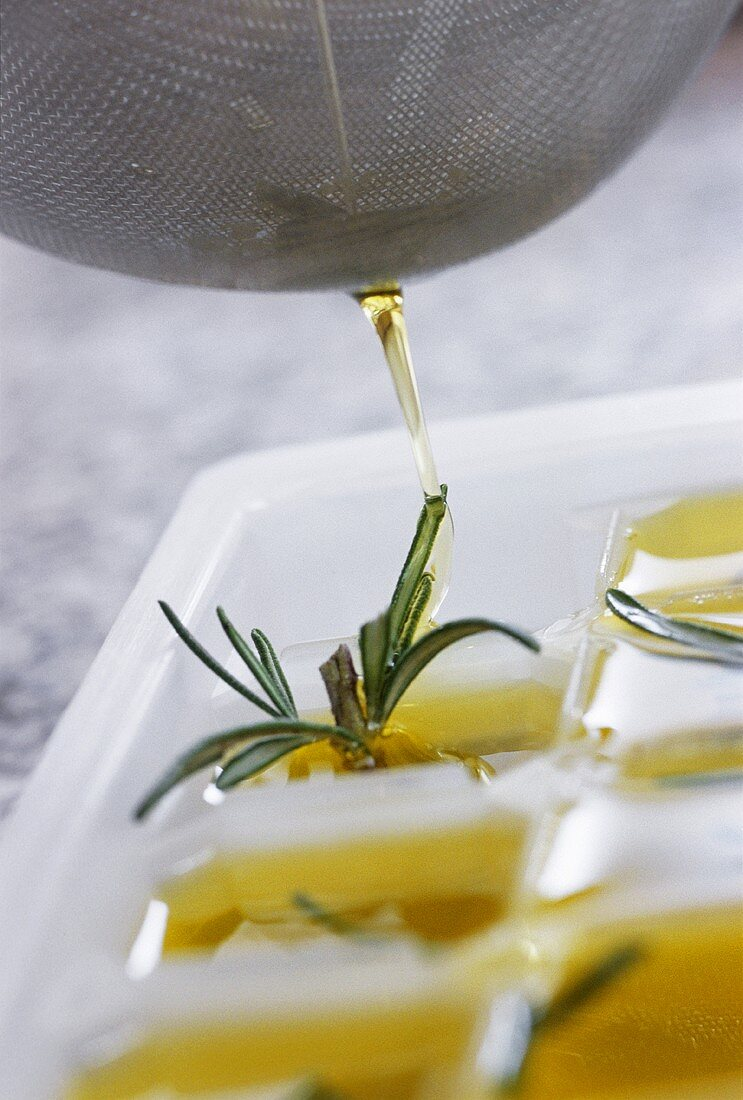 Pouring melted herb butter into ice cube mould