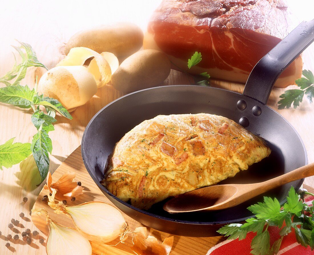 Peasant's omelette with ham, potatoes and onions in pan