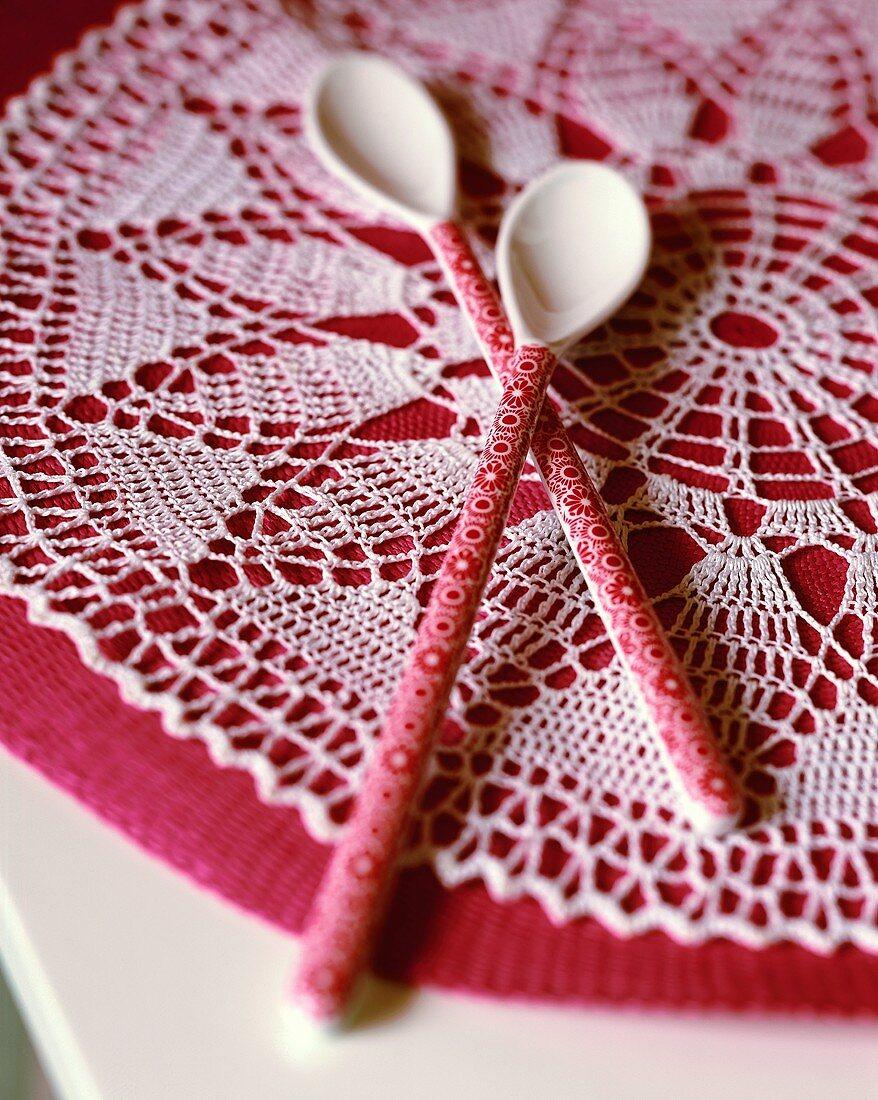 Two dessert spoons on crocheted mat