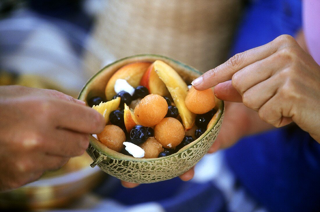 Hands reaching for pieces of fruit salad in halved melon