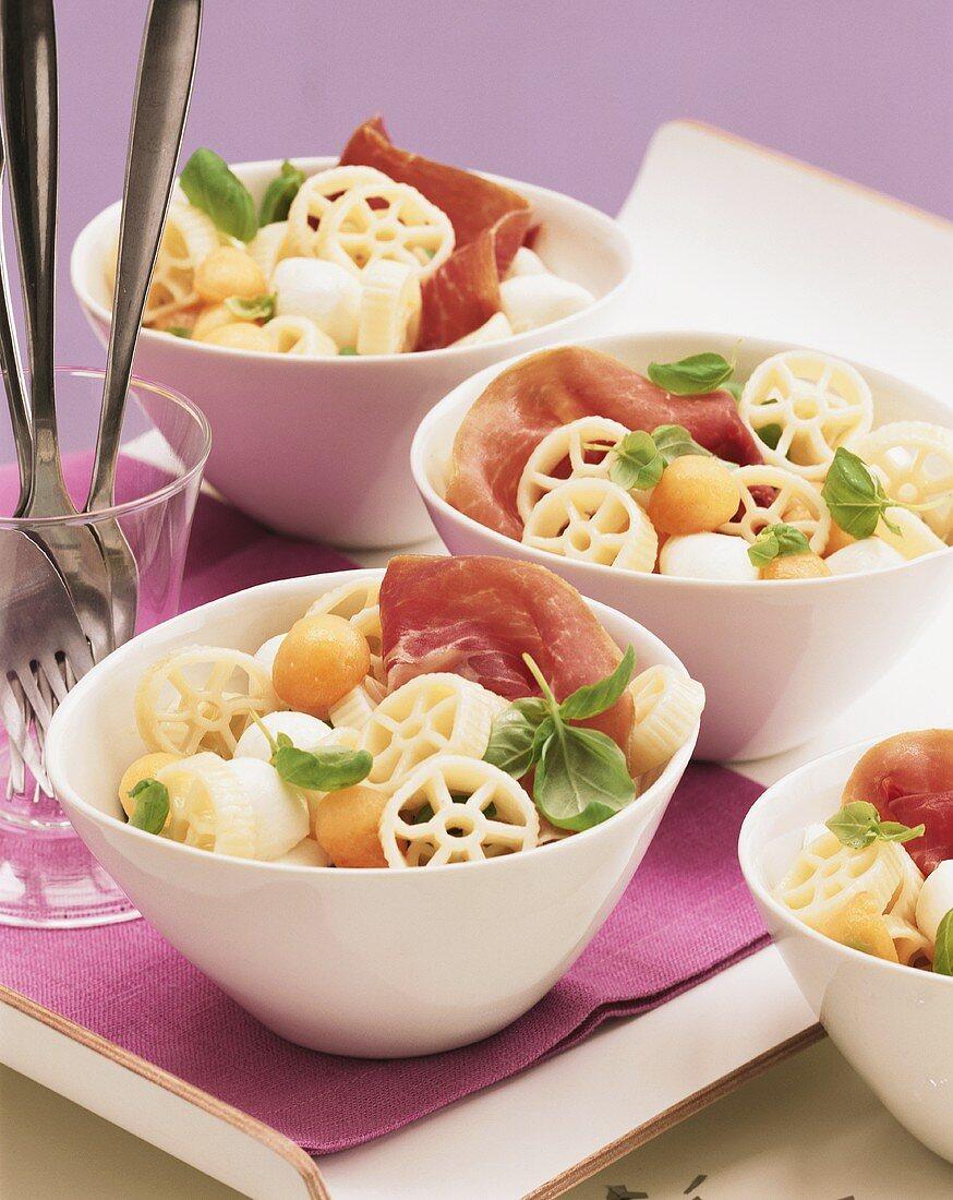 Colourful pasta salad with ham, melon and mozzarella