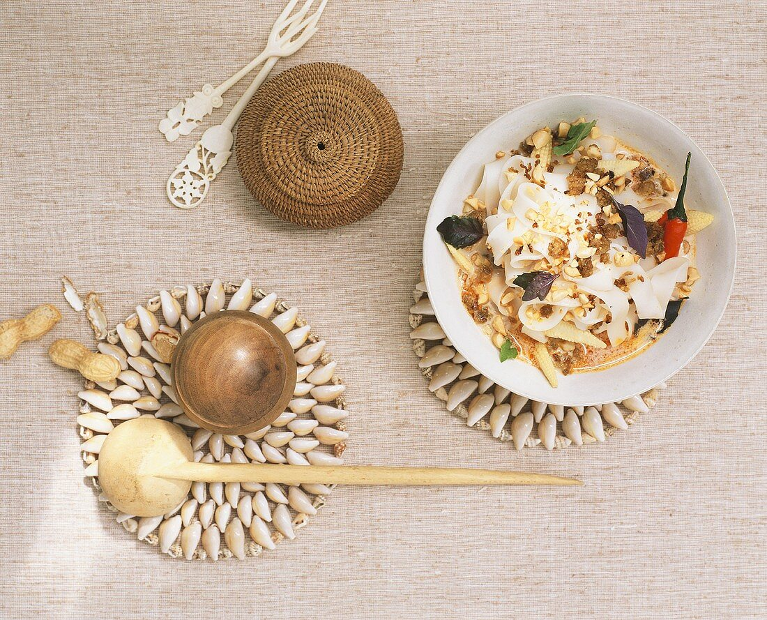 Rice noodles in curry sauce with baby corncobs and peanuts