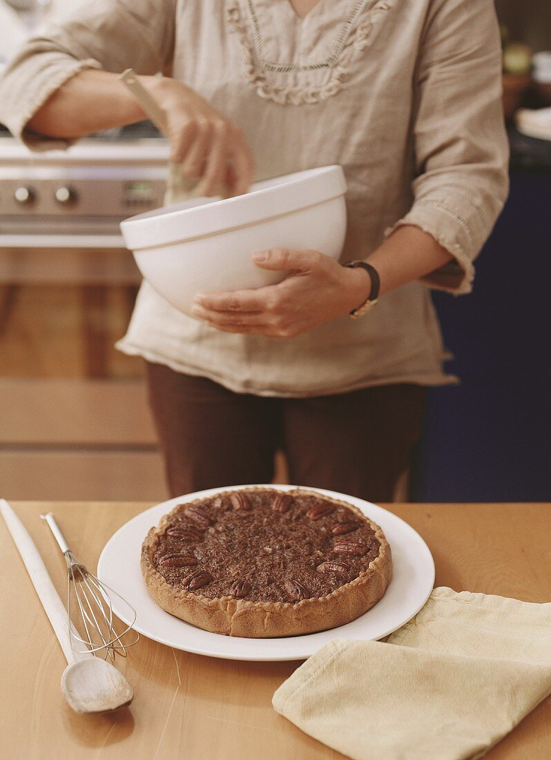 Pecan pie on kitchen table, woman with mixing bowl