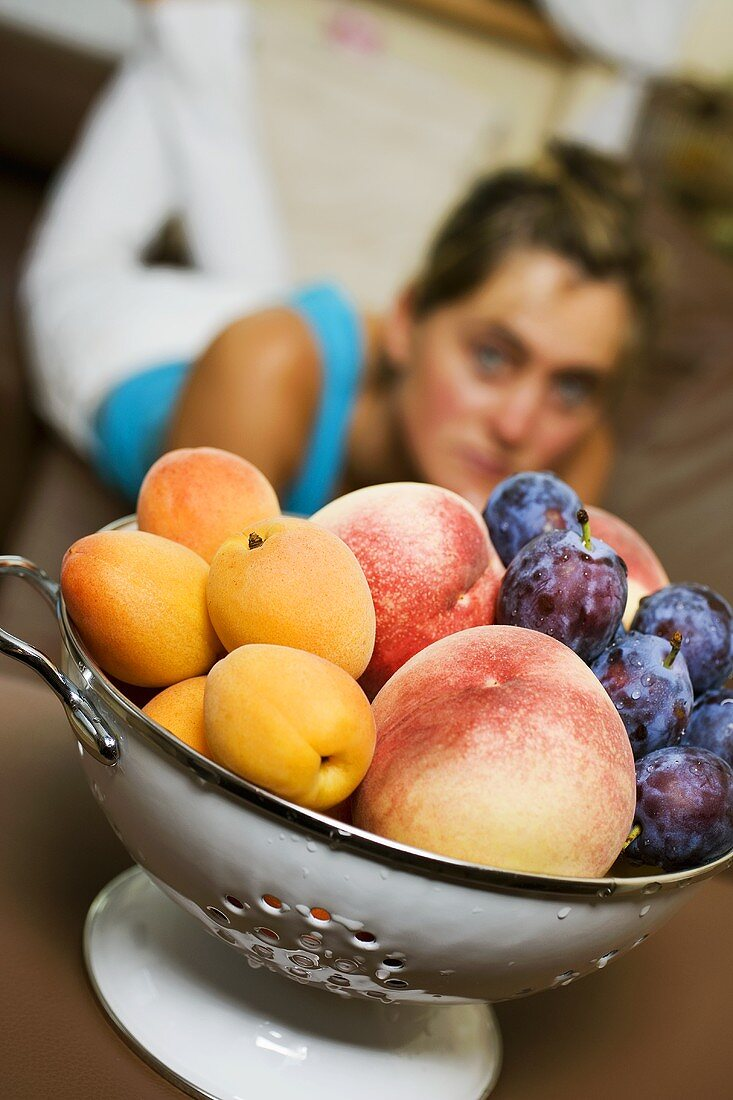 Plums, peaches, apricots in colander, woman in background