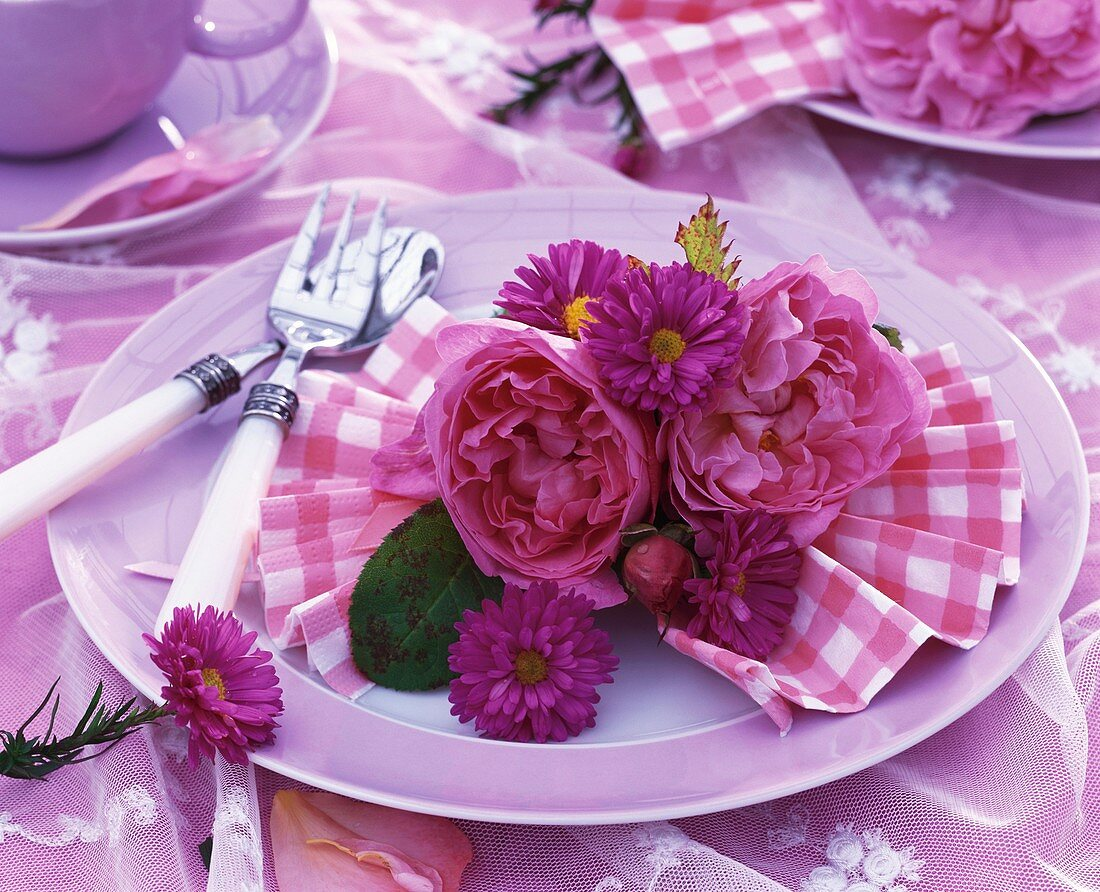 Summery place-setting decorated with roses and asters