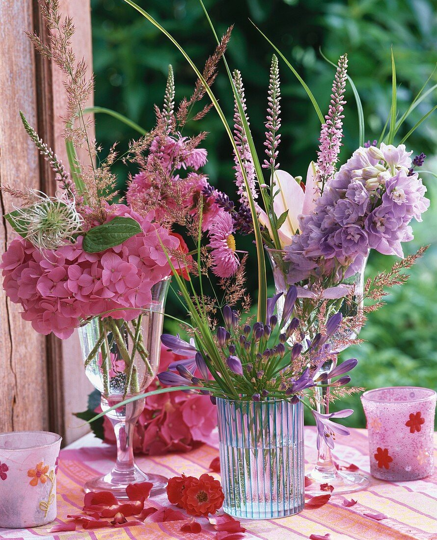Summer flowers in glasses and wind lights on garden table