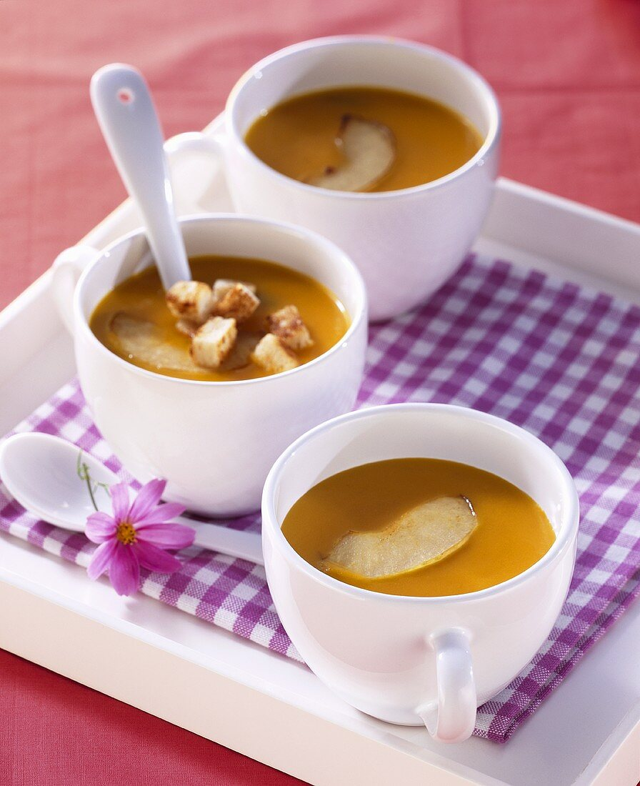 Carrot and apple soup with croutons in three cups