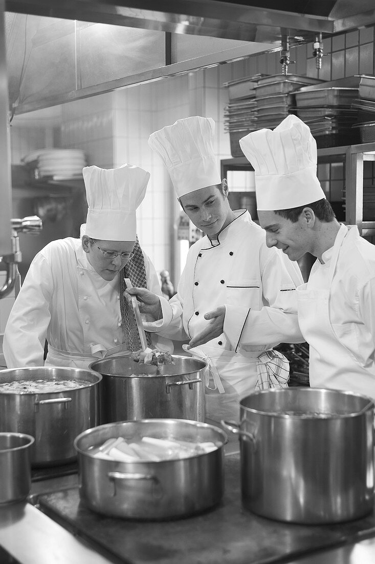 Three chefs examining the contents of a pan