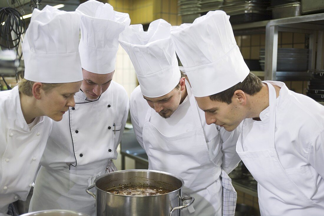 Four chefs examining the contents of a pan