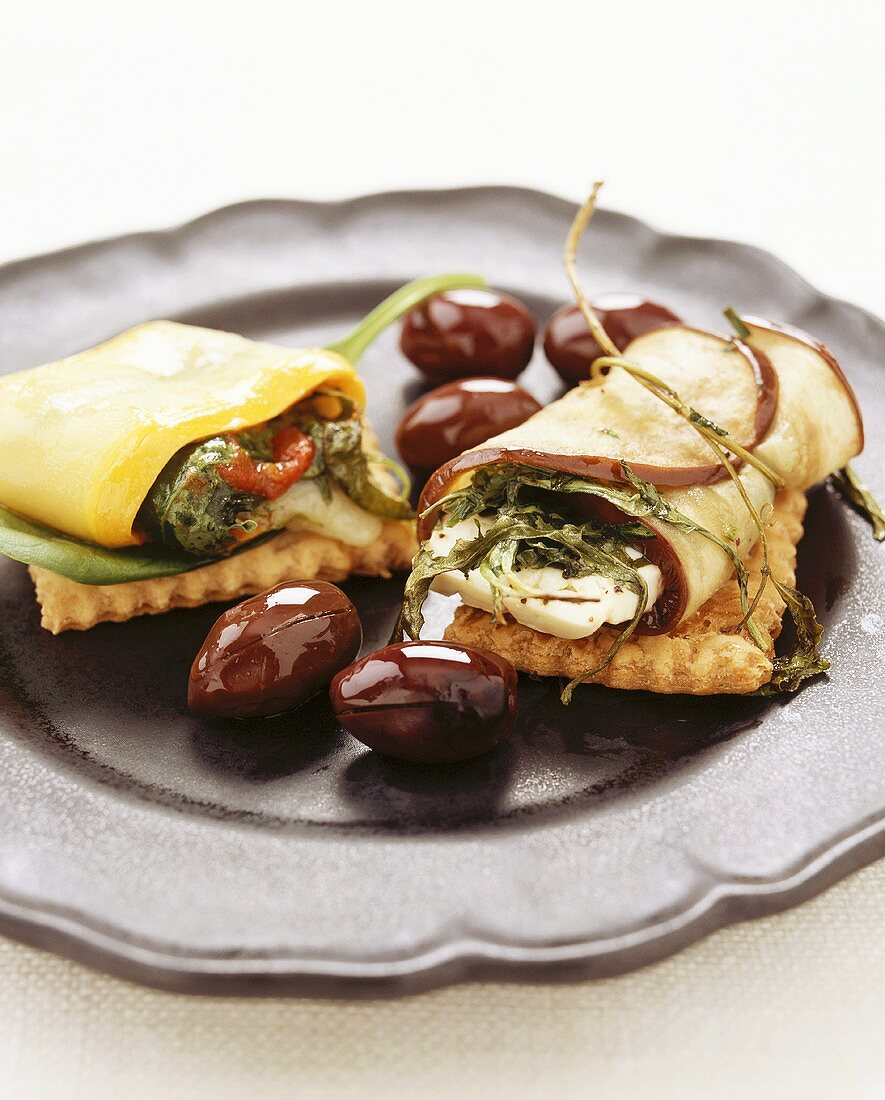 Aubergine roll with feta and courgette roll on crackers
