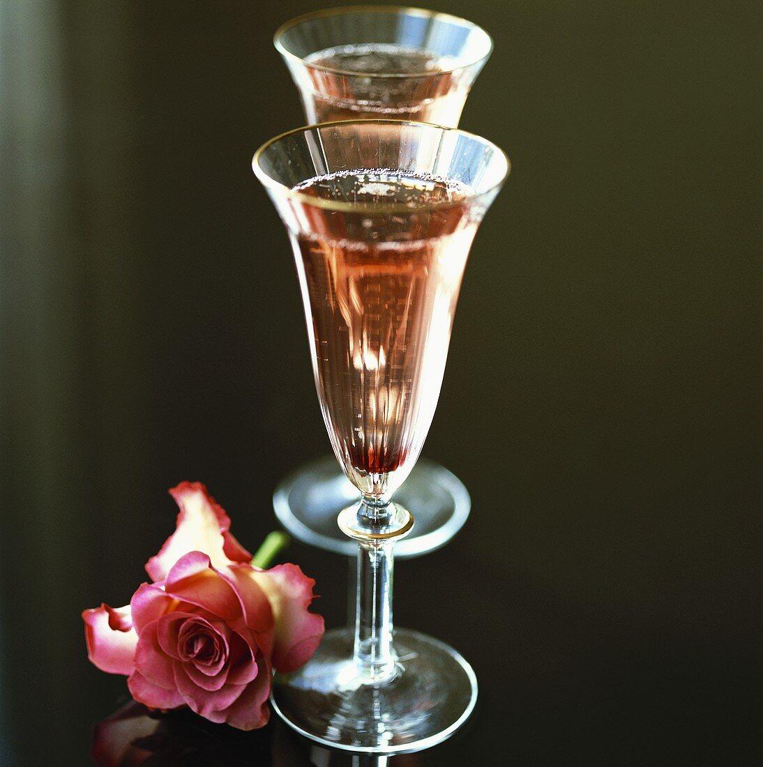 Two glasses of Kir Royal, a rose beside them
