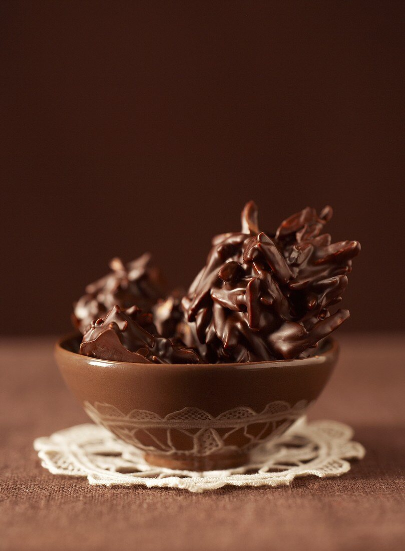 Chocolate-coated almond clusters in brown bowl