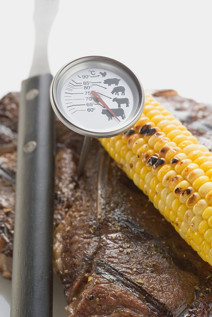 T-bone steak, meat thermometer, corn on the cob, carving fork