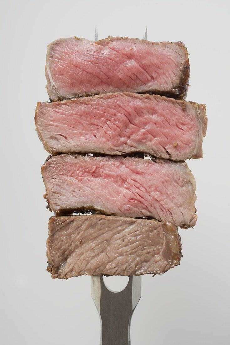 Slices of beef steak on carving fork (different degrees of cooking)