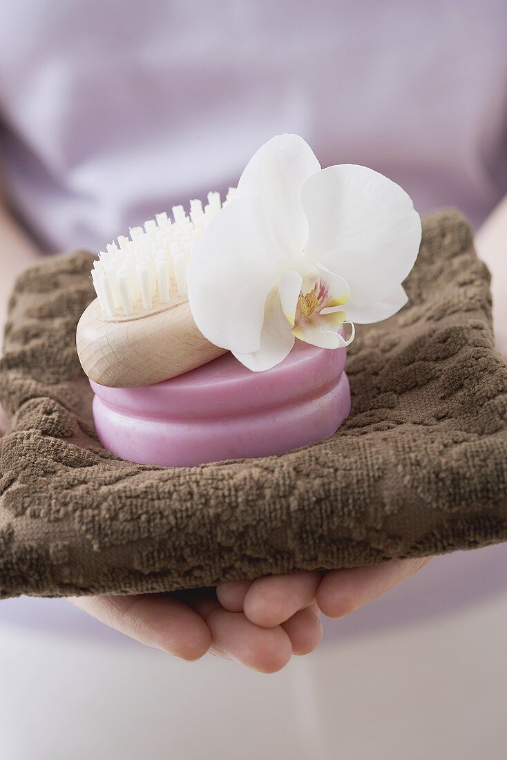 Woman holding towel, soap, brush and orchid