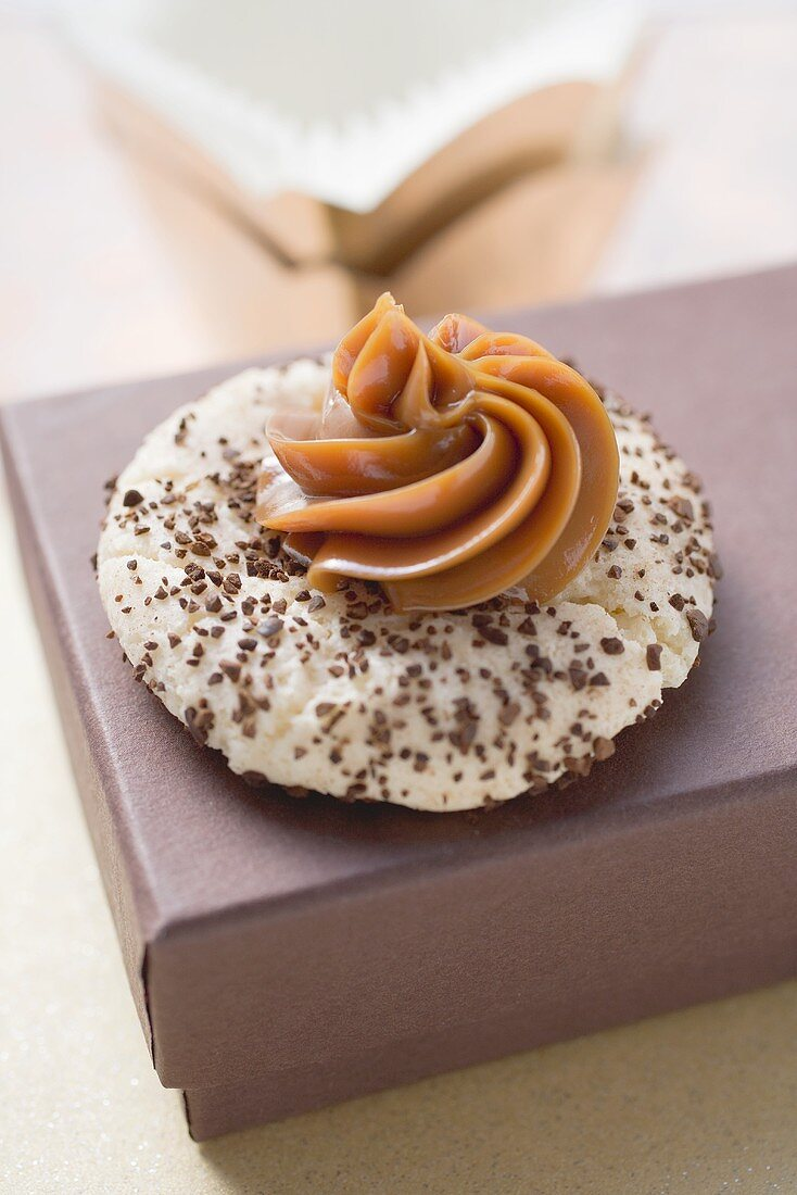 Espresso biscuit with caramel rosette on a brown box