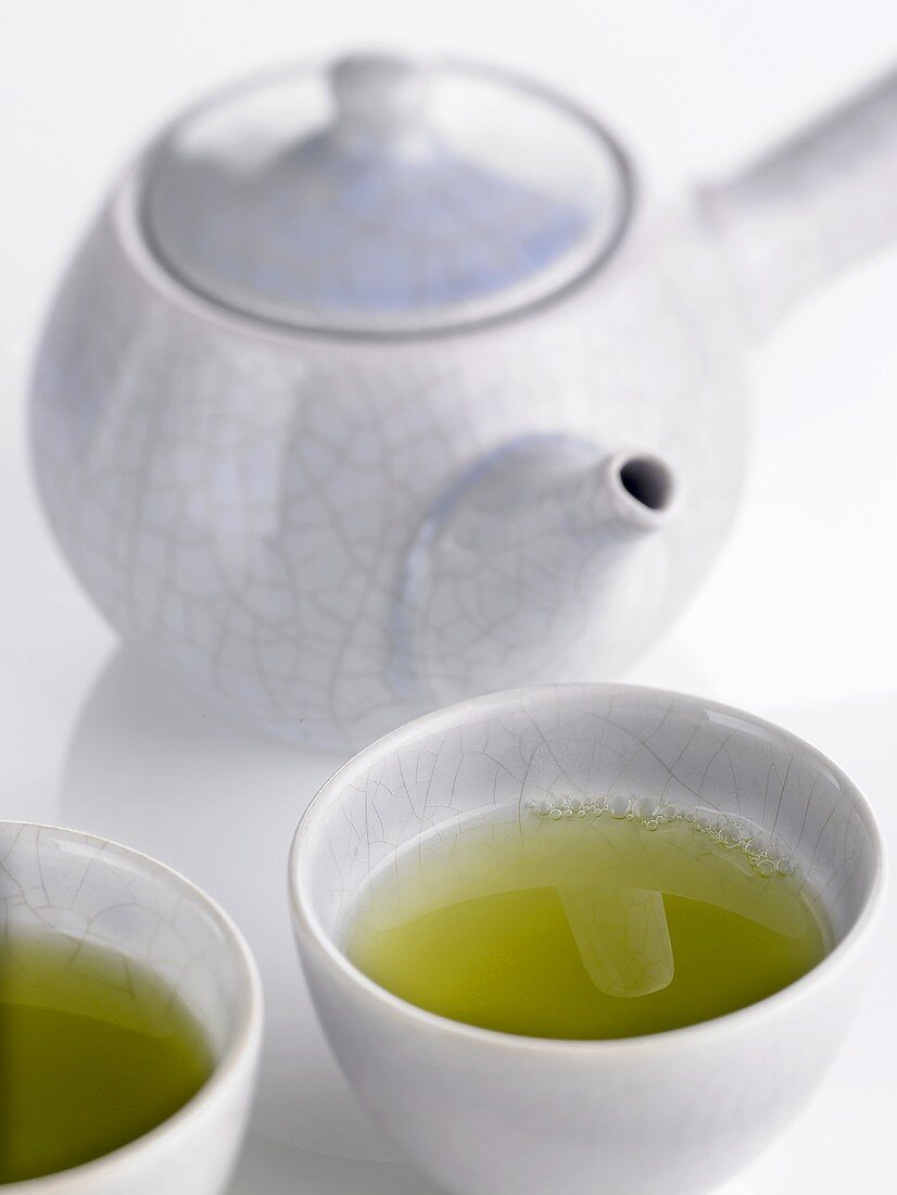 Two bowls of green tea in front of teapot