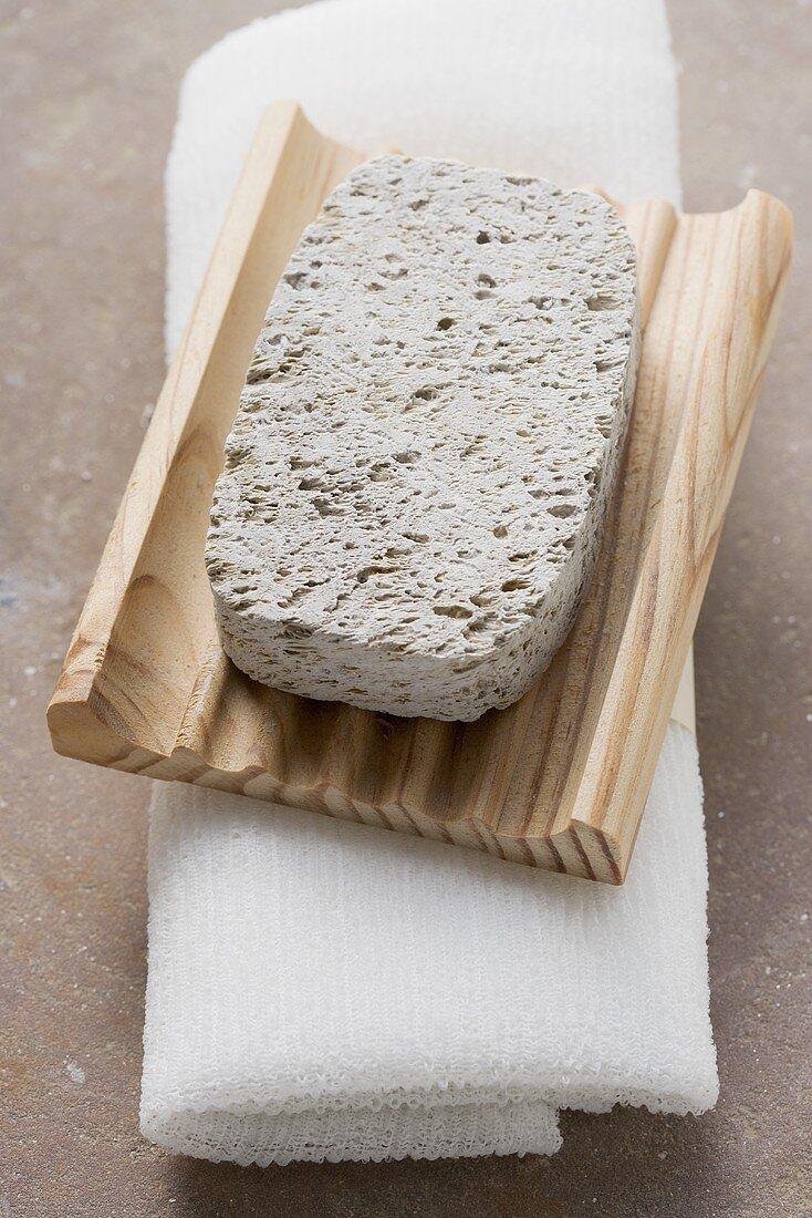 Pumice stone, wooden soap dish, towel