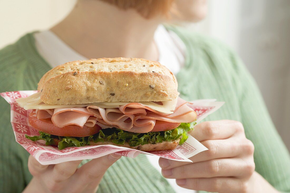 Woman holding ham and cheese sandwich on paper napkin