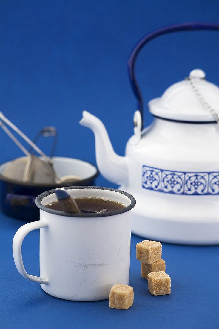 A mug of black tea, sugar cubes, kettle, tea strainer