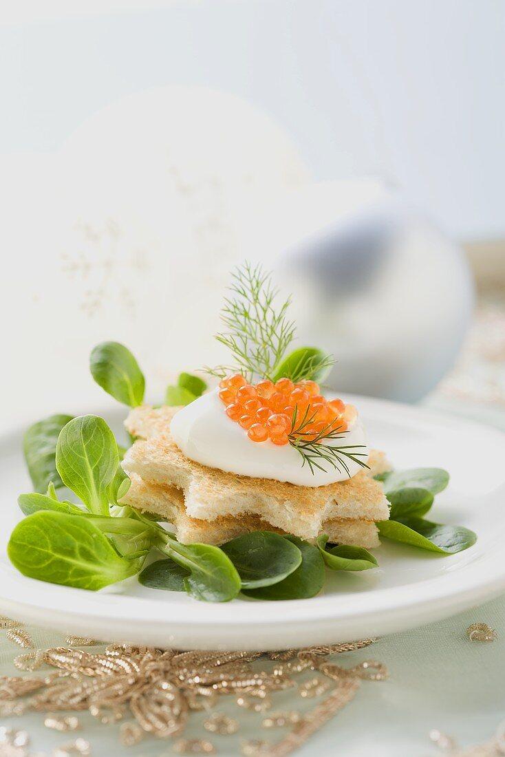 Crème fraîche and caviar on toast stars on corn salad