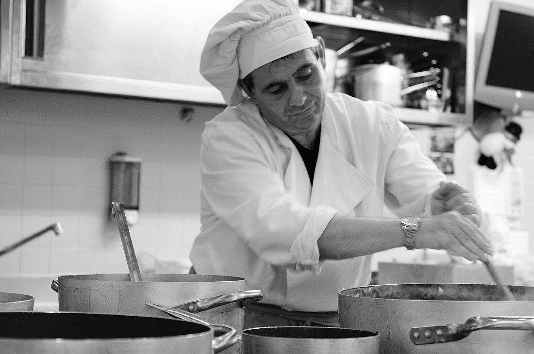Chef stirring a pan in a commercial kitchen