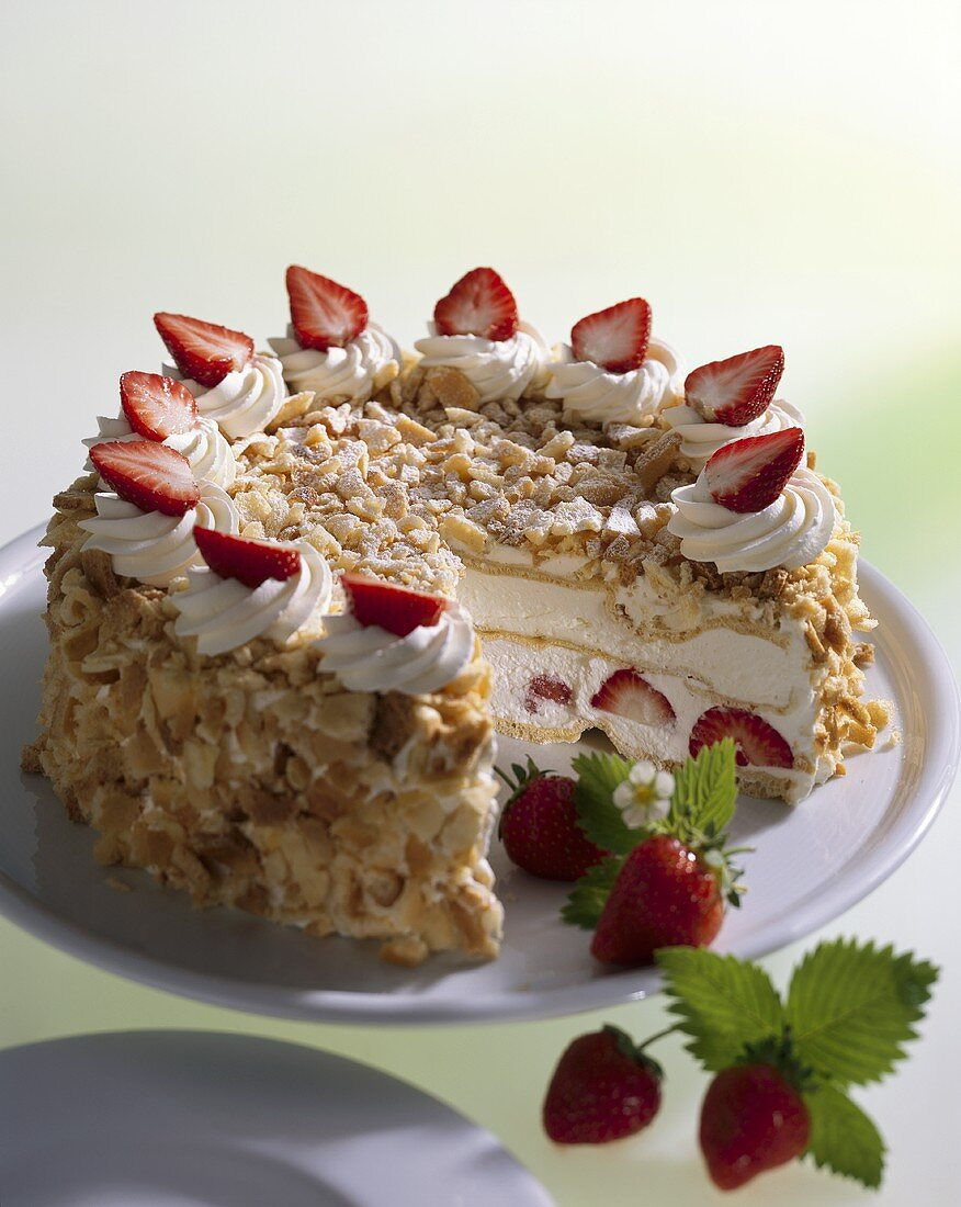 Cream cake with chopped nuts and strawberries