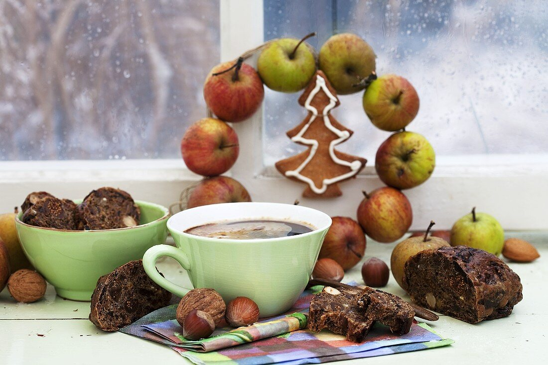 Fruit bread and a cup of coffee on a windowsill