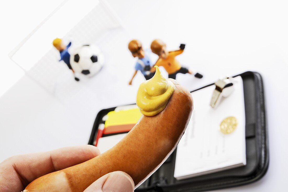 Frankfurter with mustard, note book and footballers