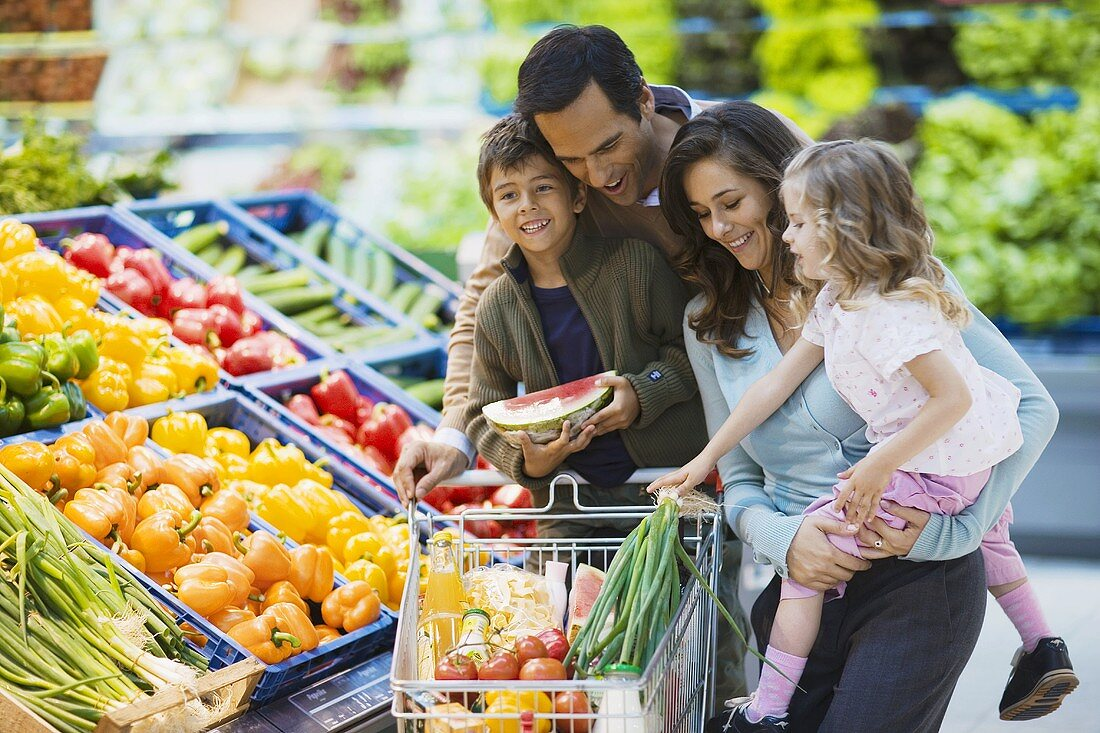 Family with shopping trolley at vegetable counter in supermarket
