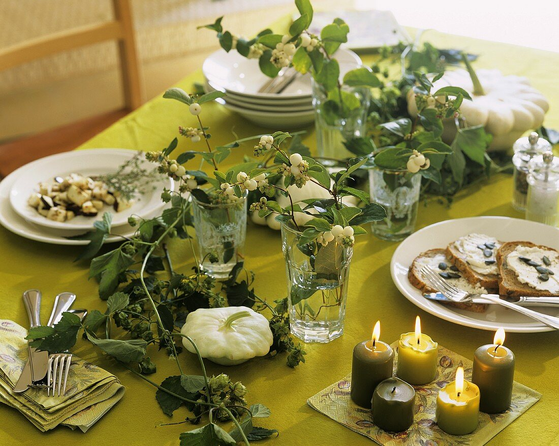 Table with autumnal decorations: snowberries, pumpkin, hops