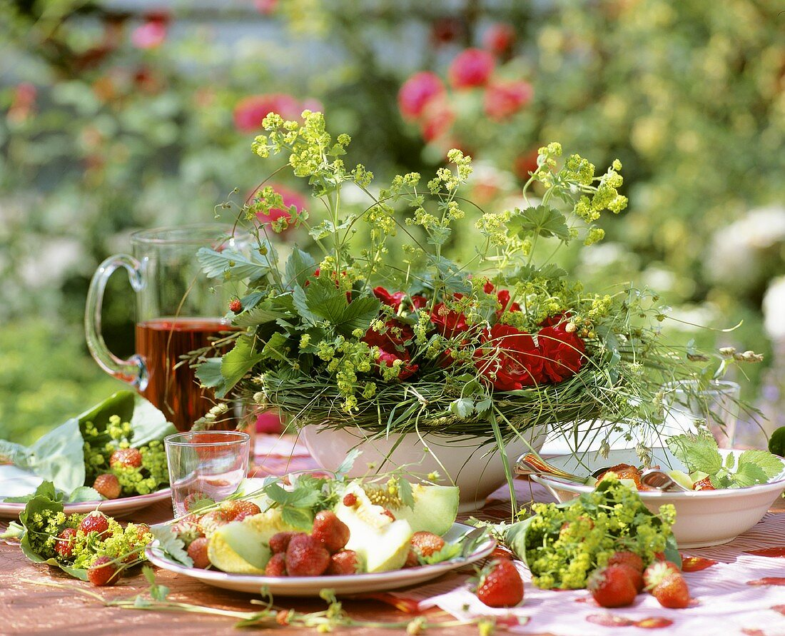 Summery table with strawberries and melon in the open air