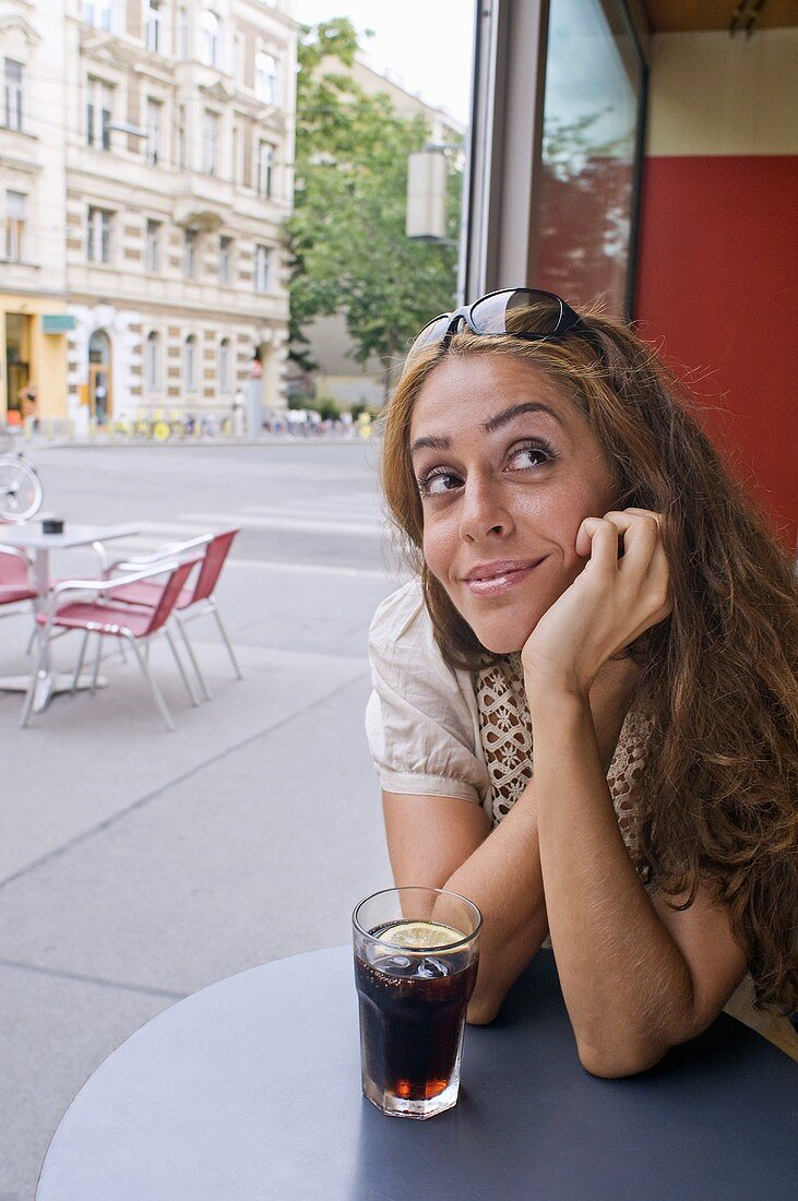 Woman with a glass of cola at a street cafe