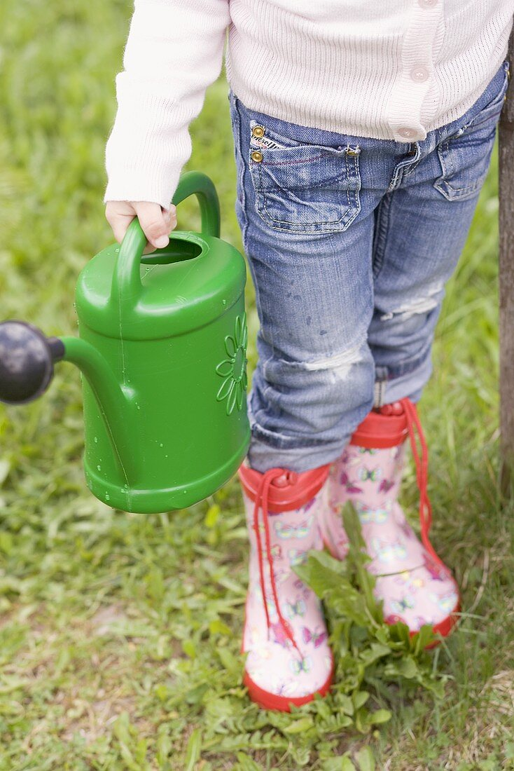 Child with watering can in garden