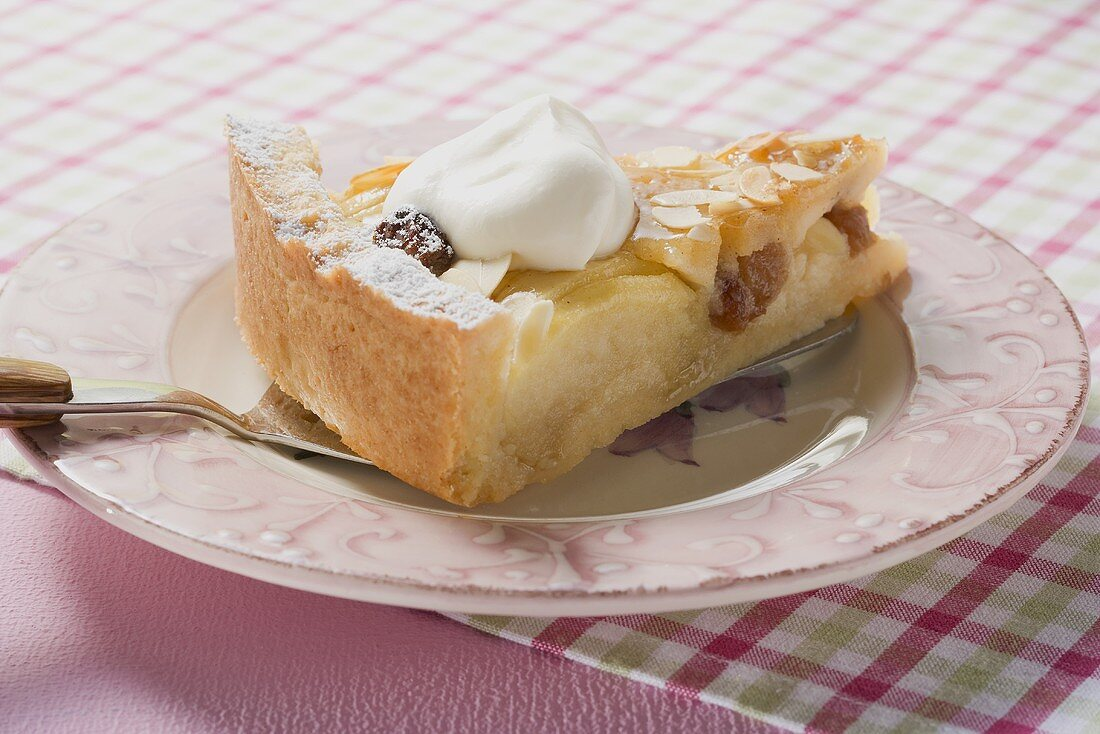 Piece of apple tart with flaked almonds and cream