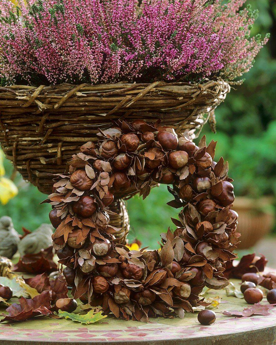 Kranz aus Kastanien und Herbstblättern, dahinter Heidekraut