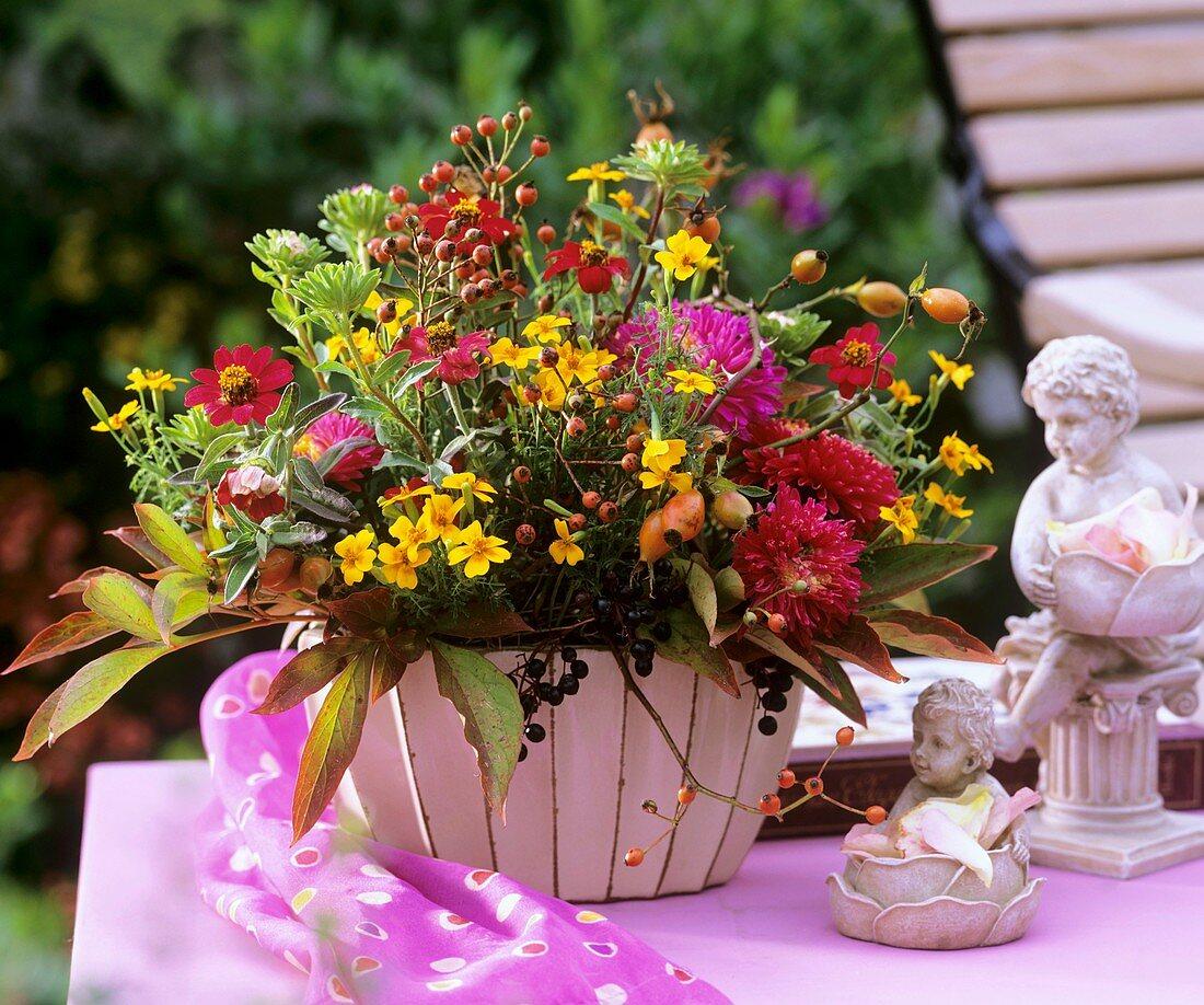 Summer arrangement: rose hips, Tagetes, Zinnias, Callistephus