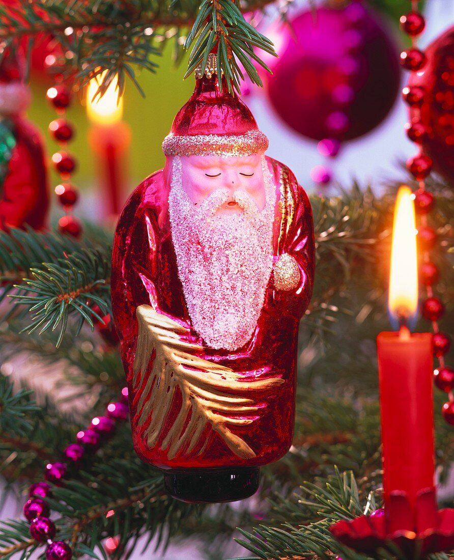 Father Christmas and burning candle on Christmas tree
