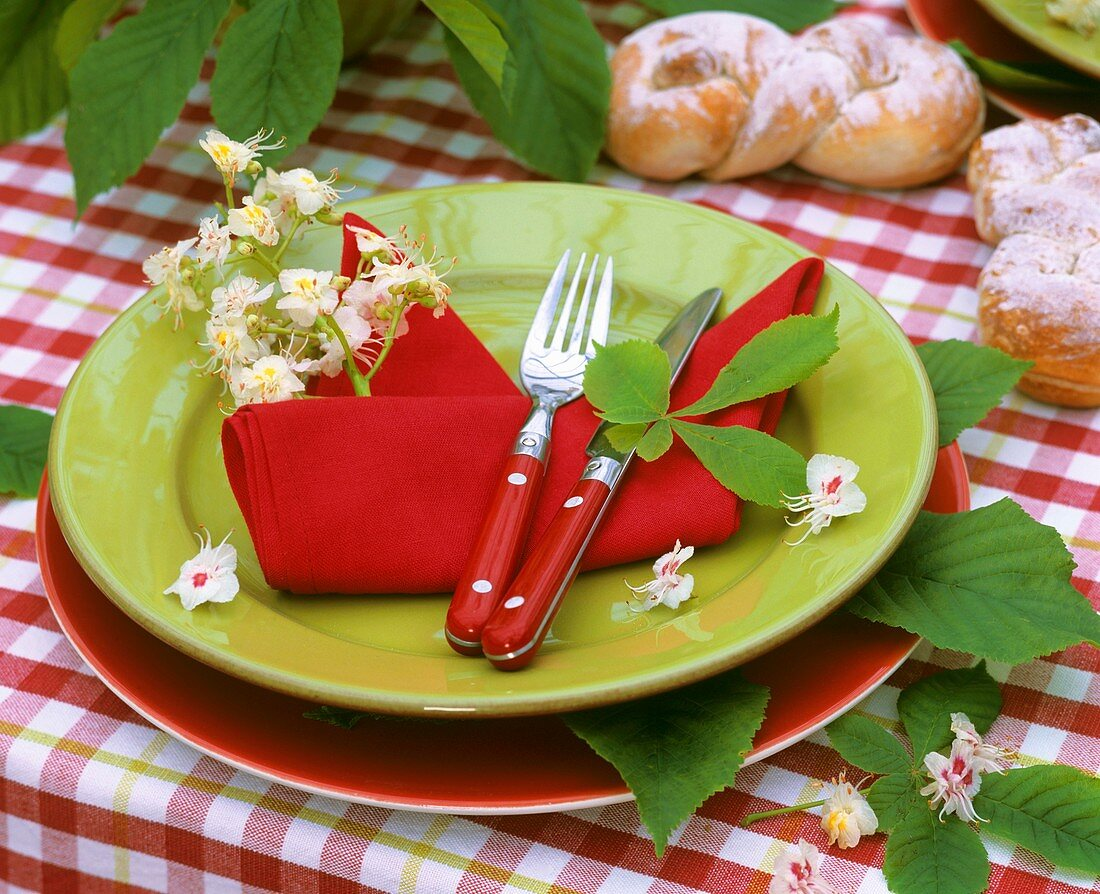Place setting decorated with horse chestnut blossom & leaves