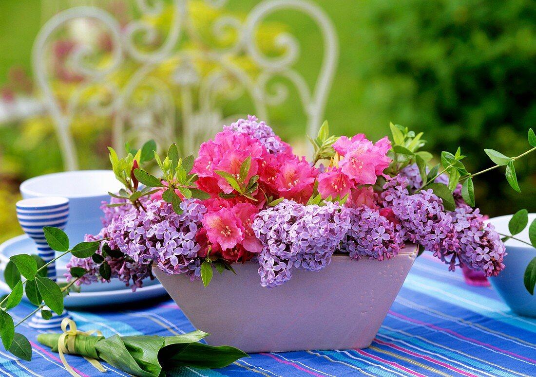 Blumenschale mit Flieder, Rhododendron und Immergrünranken