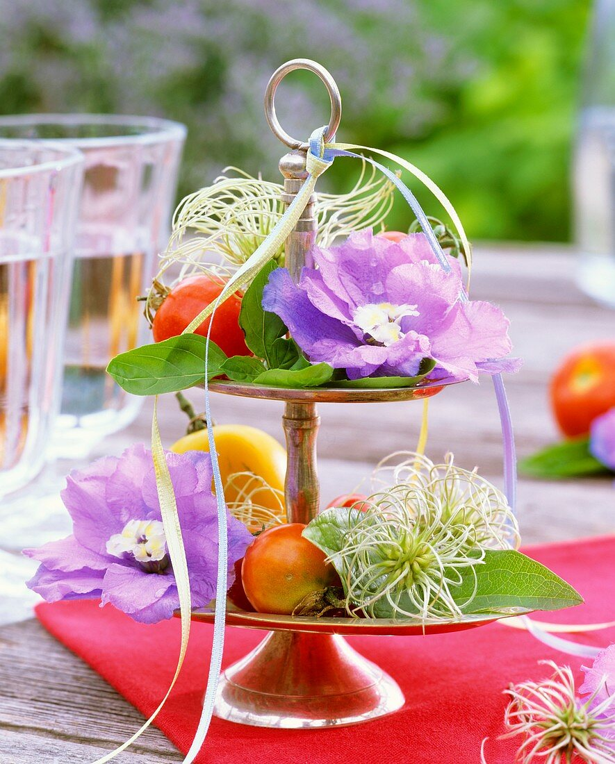 Delphiniums, clematis and basil on silver tiered stand