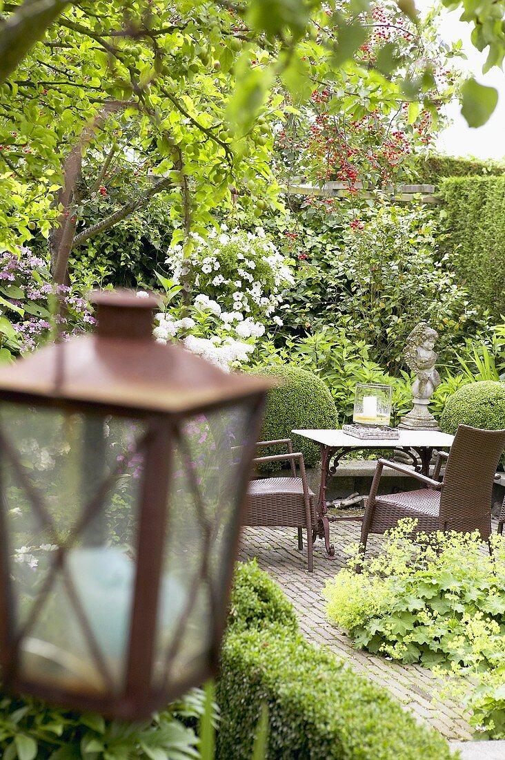 Sitting area and lantern in summery garden